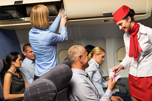Flight attendant taking care of passengers on a plane
